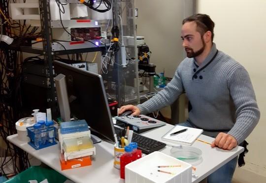 Il Dr. Simone Brusco che lavora al suo set-up di elettrofisiologia per analizzare l'attività delle cellule